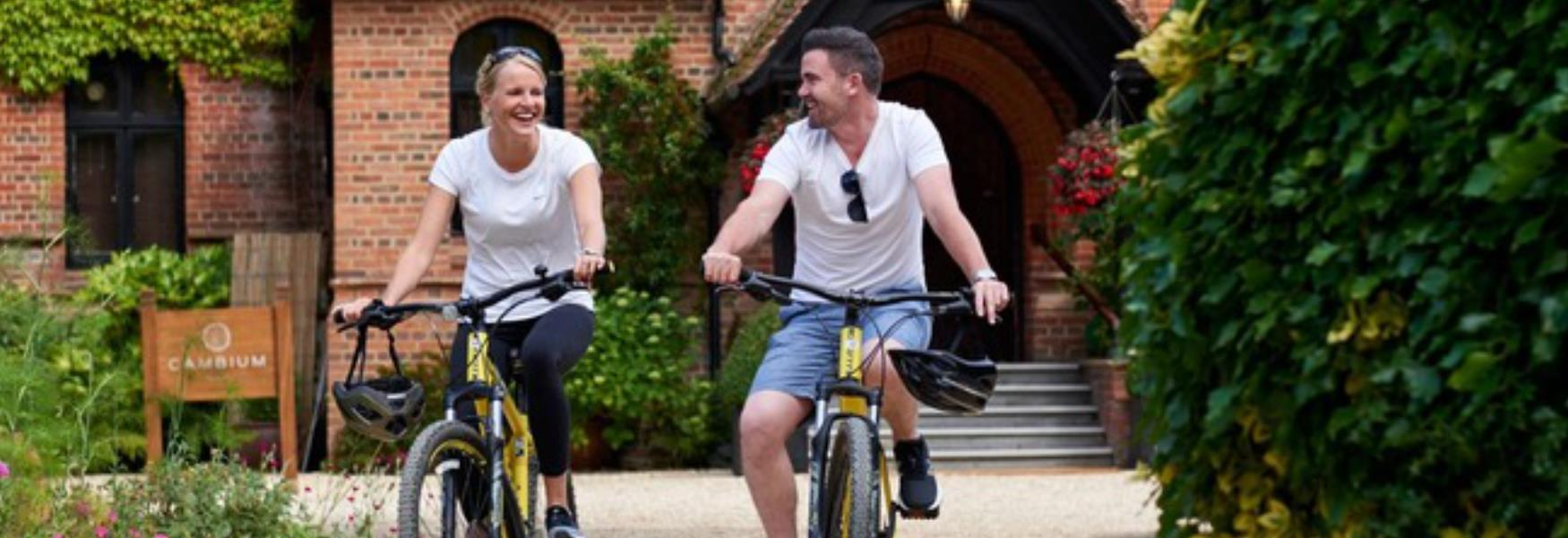 Couple cycling outside Careys Manor Hotel in the New Forest