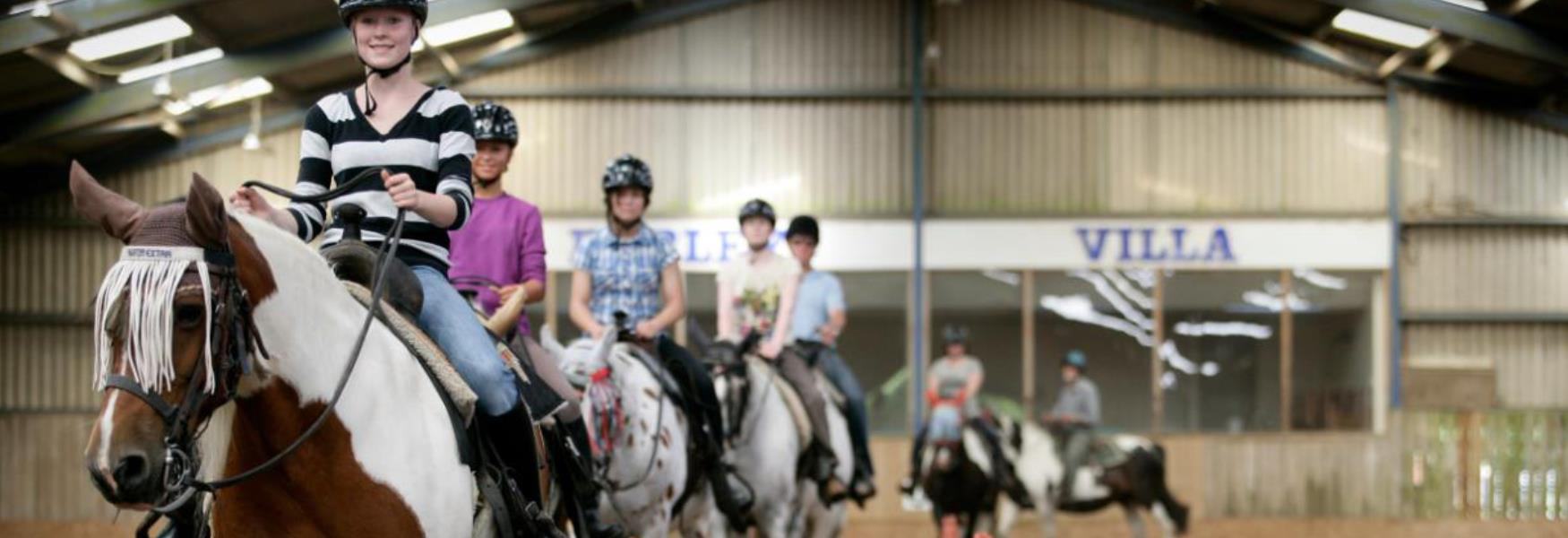 group horse riding inside at Burley Villa School of Riding in the New Forest