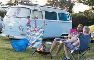 Relaxing by campfire in front of VW campervan