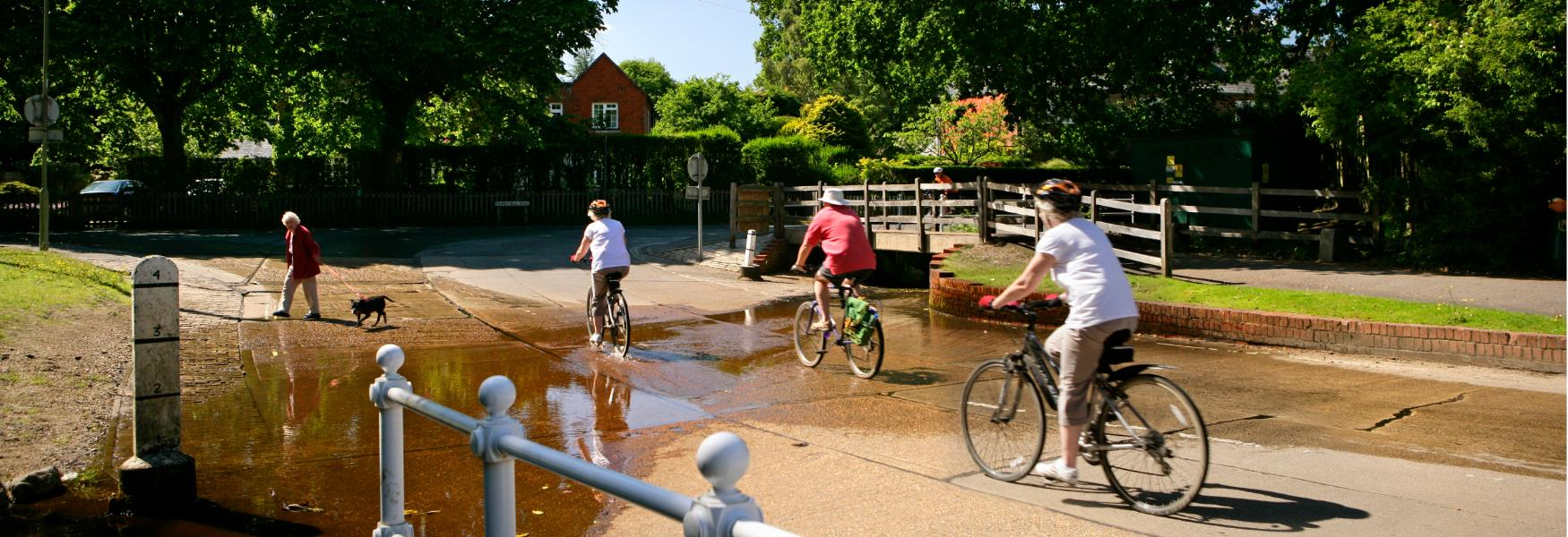 Cycling through ford in Brockenhurst in the New Forest