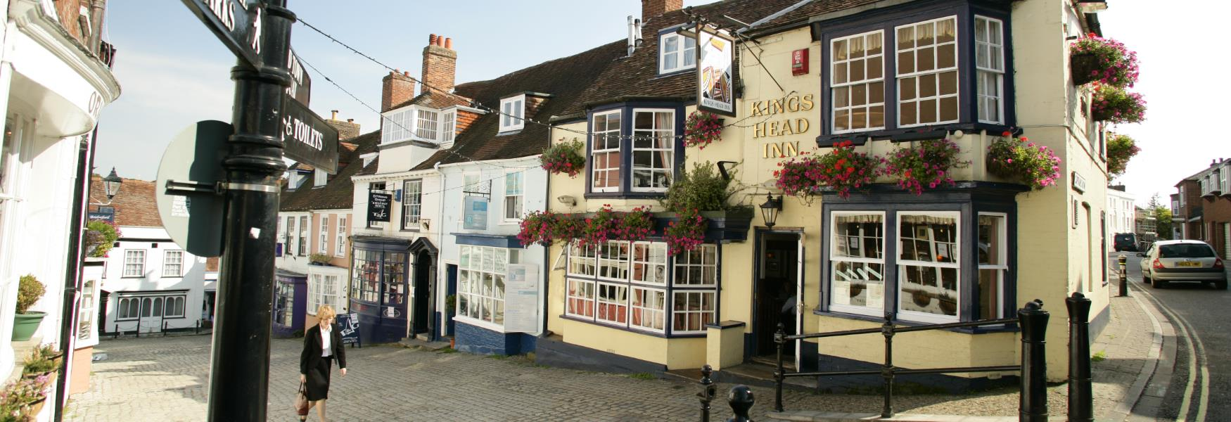 Shops and Pubs down cobbles in Lymington High Street in the New Forest