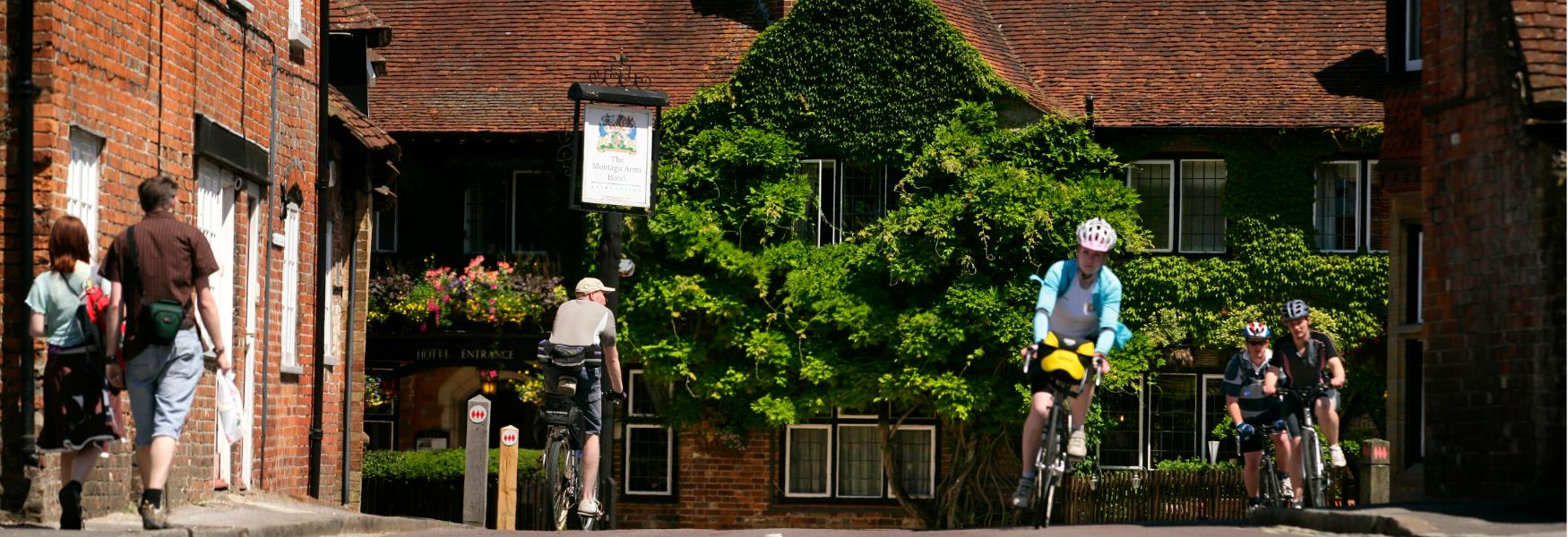 Cycling through Beaulieu Village High Street in the New Forest