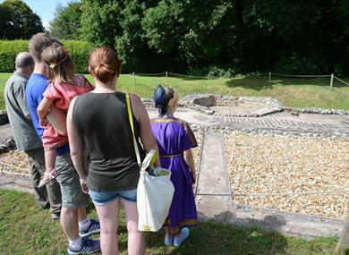 Family looking at Roman bathhouse ruins in the new forest